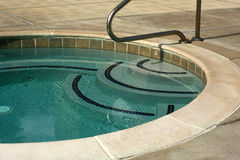 Jacuzzi. Close-up of decorative steps with navy tile and clear blue water of outdoor jacuzzi Stock Photography