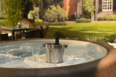 Jacuzzi, hot tub. For recreation and luxury relaxation. A tablet with champagner and glasses is swimming on the top of the whirling water. Image taken outside stock image