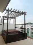 Jacuzzi on roof top. An image of a new jacuzzi set on the rooftop balcony of a new condominium pent house residence.  With wooden finishing and shelter frame for Royalty Free Stock Images