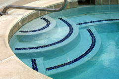 Jacuzzi Steps. Close-up of steps with decorative navy tile and clear blue water of jacuzzi Stock Images