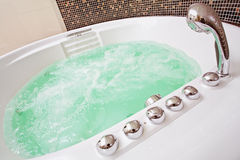 Jacuzzi with swirling water. And brown mosaic in bathroom royalty free stock photography