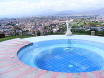 Jacuzzi With A View. Circular jacuzzi overlooking Fethiye Bay in turkey. A statue looks out across the city Stock Photo
