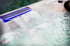 Jacuzzi waterfall bath with water. Water jet close-up stock photography