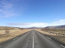 Jadący na pustej otwartej asfaltowej drodze w kierunku pasma góry zakrywać w śniegu na niebieskie niebo słonecznym dniu, biznesow Zdjęcia Stock