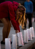 Girl lights luminary for Melissa Jenkins Memorial. Jada Berry of Lyndonville Vermont lights one of the dozens of lumineries that lines the sidewalks in front of Royalty Free Stock Photo