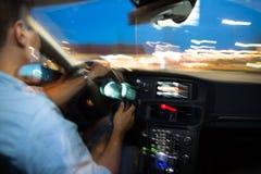 Jadący samochód przy nocą - młody człowiek jedzie jego nowożytnego samochód Zdjęcia Stock