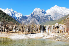 The Jade Dragon Snow Mountain. Lake of the Jade Dragon Snow Mountain, blue sky, blue clean water, tree, forest, rock, waterfall royalty free stock image