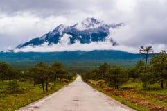 Jade Dragon Snow Mountain (Yulong Xueshan) i moln Royaltyfri Foto