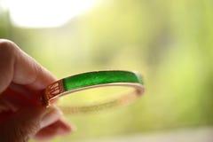 Jade verde insertado en una pulsera del oro Fotos de archivo