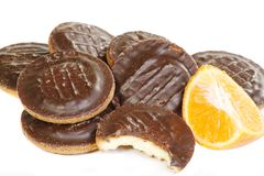 Jaffa cakes. Pile of chocolate coated jaffa cakes with a segment of orange on a white background Royalty Free Stock Photo