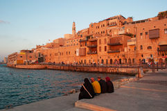 Jaffa, Tel Aviv, Yafo, Israel, Middle East. A muslim family seated at the port of Jaffa with view of the Old City at sunset on August 31, 2015. Jaffa is the Royalty Free Stock Images
