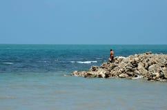 Man on rocks looks out to ocean from rocky beach Jaffna Peninsula Sri Lanka. Jaffna, Sri Lanka - February 19, 2017: A Sri Lankan Tamil man looks out towards the stock photography