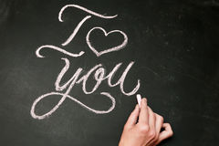 jag älskar dig Handskrivet meddelande på en svart tavla med handen Royaltyfri Foto