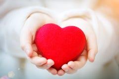 Jag älskar dig mamman, dag för moder` s Röd hjärta i händer av lilla flickan Symbol av förälskelse och familjen arkivbild