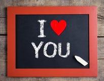 Jag älskar dig med hjärta på en torkdukebakgrund på den lilla svart tavla Arkivbild