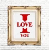 Jag älskar dig ordet i den guld- tappningfotoramen på den vita tegelstenväggen, förälskelsebegrepp Royaltyfri Foto