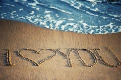 Jag älskar dig - som är skriftlig i sanden Arkivfoto