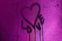 Jag älskar dig som är skriftlig på kondensationsexponeringsglas med purpurfärgat ljus Royaltyfri Bild
