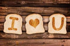 Jag älskar dig som är skriftlig på rostade skivor av bröd, på träplankabakgrund Arkivbilder