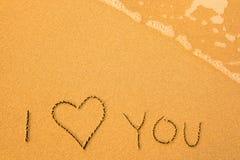 Jag älskar dig - som är skriftlig vid handen i sand på en strand Arkivfoton