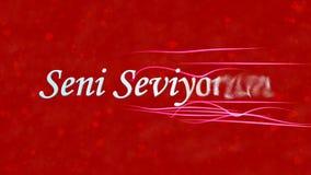 Jag älskar dig text i turkSeni Seviyorum vänd för att damma av från rätt på röd bakgrund Royaltyfri Bild