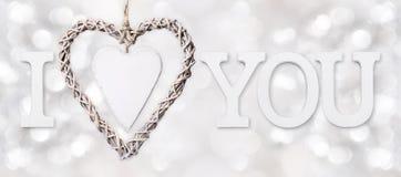 Jag älskar dig text med hjärta av vävt trä på suddigt ljus för silver Royaltyfri Foto