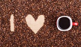 JAG ÄLSKAR KAFFE som göras av kaffebönor och den röda kaffekoppen Royaltyfri Bild