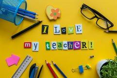 Jag älskar min lärare - text som göras med sned bokstäver på det gula skrivbordet med kontors- eller skolatillförsel på elevtabel Royaltyfri Foto