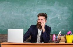 Jag är din nya lärare Skolalärare som är klar att starta kurs Läraren sitter på skrivbordet med bärbara datorn tillbaka begreppss arkivbilder