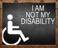Jag är inte mitt handikapp som är skriftligt på svart tavla arkivbild