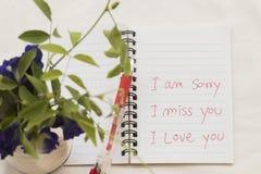 Jag är ledsen att jag missa dig som jag älskar dig meddelandekortet skriver på anteckningsboken med blommor Arkivbild
