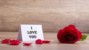 Jag älskar dig kortet med den röda rosen på tabellen Royaltyfri Fotografi