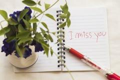 jag missa dig som jag älskar dig, skriver meddelandekortet på anteckningsboken med blommor Royaltyfria Foton