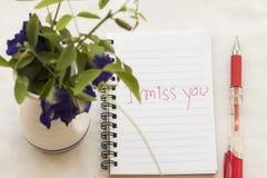 jag missa dig som jag älskar dig, skriver meddelandekortet på anteckningsboken med blommor Arkivfoto