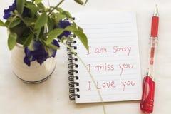 Jag missa dig som jag är ledsen att jag älskar dig meddelandekortet skriver på anteckningsboken med blommor Royaltyfri Fotografi
