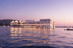 Jag nivas lake palace hotel at dusk. Jag nivas lake palace on lake pichola at dusk. This luxury hotel sits on an artifical island in the middle of the lake. It`s Royalty Free Stock Photo