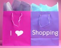 Jag shoppingmeddelandet för hjärta (förälskelse) på rosa och purpurfärgad shopping hänger lös. Arkivbilder