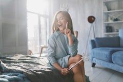 Jag vet! Gullig liten flicka som gör en gest och ler, medan spela intelligens Arkivbild