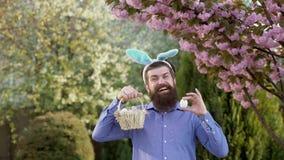 Jaga ägget och rolig påskdag Bärande kaninöron för skäggig man och ha påskägg Förvånat bära för kaninman arkivfilmer