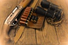 Jaga geväret och ammunitionar ligger på träbakgrund royaltyfria foton
