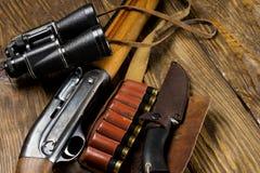 Jaga geväret och ammunitionar ligger på träbakgrund arkivbilder