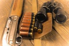 Jaga geväret och ammunitionar ligger på träbakgrund royaltyfri foto