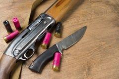 Jaga geväret och ammunitionar ligger på träbakgrund kopiera avstånd arkivfoto
