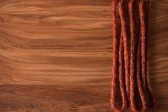 Jaga korvar rökte för öl på en träbakgrund Rå rökte köttprodukter Hemlagad mat som hemma lagas mat arkivbild