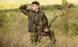 Jaga tillståndet Skäggig jägare att spendera fritidjakt Jägarehållgevär Fokus och koncentration av den erfarna jägaren royaltyfri bild