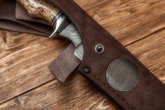 Jagddamaskus-Stahlmesser handgemacht auf einem hölzernen Hintergrund, Nahaufnahme stockfotos