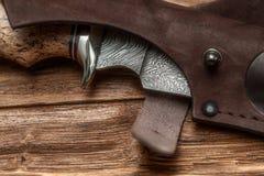 Jagddamaskus-Stahlmesser handgemacht auf einem hölzernen Hintergrund, Nahaufnahme lizenzfreie stockbilder