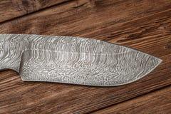 Jagddamaskus-Stahlmesser handgemacht auf hölzernem Hintergrund stockbilder