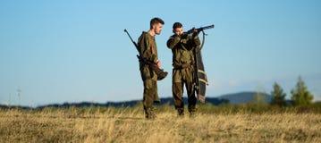 Jagdfähigkeiten und Waffenausrüstung Wie Drehungsjagd in Hobby Freundschaft von Mannjägern Armeekräfte tarnung stockfotografie