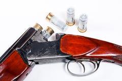 Jagdschrotflinte und -munition auf weißem Hintergrund Stockfoto